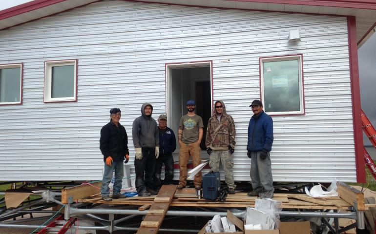 Aaron Cooke, in the T-shirt and blue hat, poses in front of an efficient house he helped design after he and Newtok residents built it at the new village site of Mertarvik in 2016. Photo by Molly Rettig.