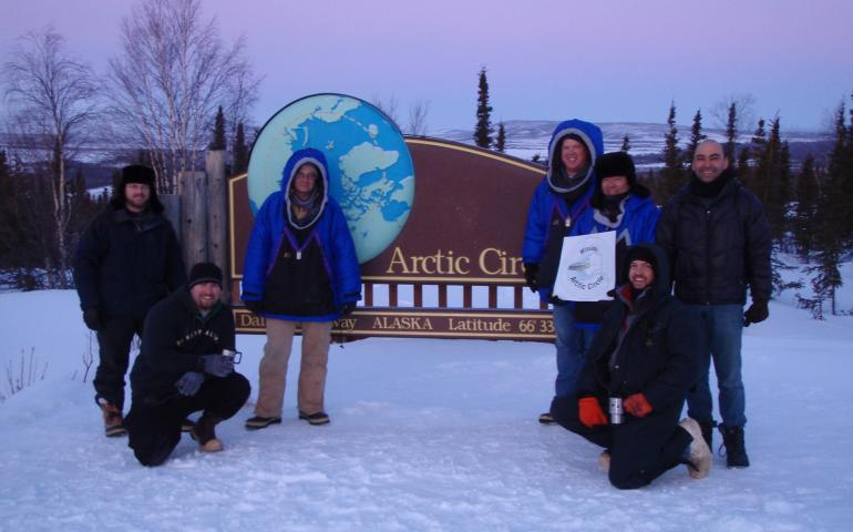 "From left, Ryan West, Shawn Freitas, John Whittington, Doug Morrow, Bernie Tao, Darrin Marshall, and Andy Soria pose at the Arctic Circle pull-out on the Dalton Highway, where they camped in March 2009 to test the cold-weather performance of ""Permaflo Biodiesel."" Photo courtesy Darrin Marshall."