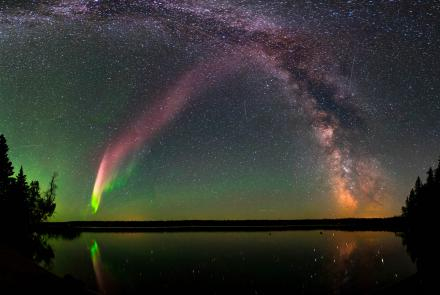 The Strong Thermal Emission Velocity Enhancement, visible as a pink band rising from the lower left to upper right of this photograph, appears with the Milky Way over Childs Lake, Manitoba, Canada. Image courtesy of Krista Trinder and NASA