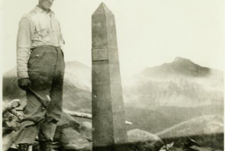 A man working with the International Boundary Commission in the early 1900s poses next to one of more than 200 obelisks that line the Alaska/Canada border. NOAA Photo Library.