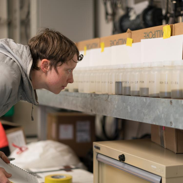Steffi O'Daly looks at sea water samples from Bering Strait aboard the UAF research ship Sikuliaq. Photo by Andrew McDonnell.