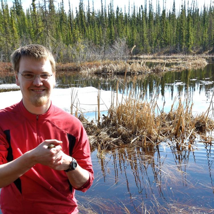 UAF doctoral student Don Larson with a wood frog he captured in Ballaine Lake on the university campus in Fairbanks. Oivind Toien photo.