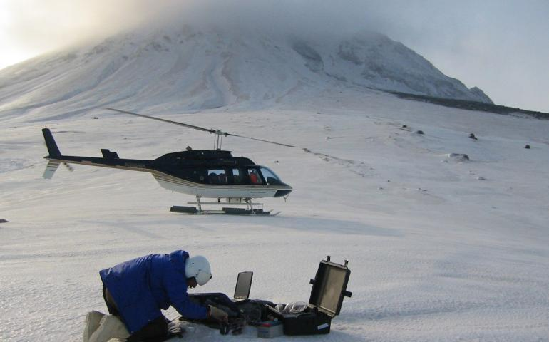 Seismologist John Power, with the U.S. Geological Survey and the Alaska Volcano Observatory, transfers data from the campaign broadband seismometer AU14 on the northeast flank of Mt. Augustine. A debris fan below the northeast chute is visible in the upper right of the image. Photo by Max Kaufman, AVO/UAF GI